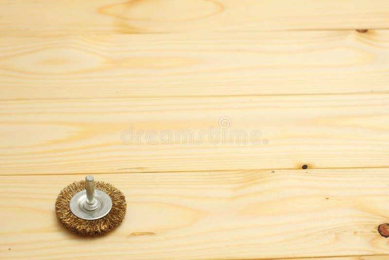 heller hölzerner Hintergrund mit rundem Metalldraht-Bürstenwerkzeug für mechanische Reinigung des Metalls und des Holzes und Rost lizenzfreie stockbilder
