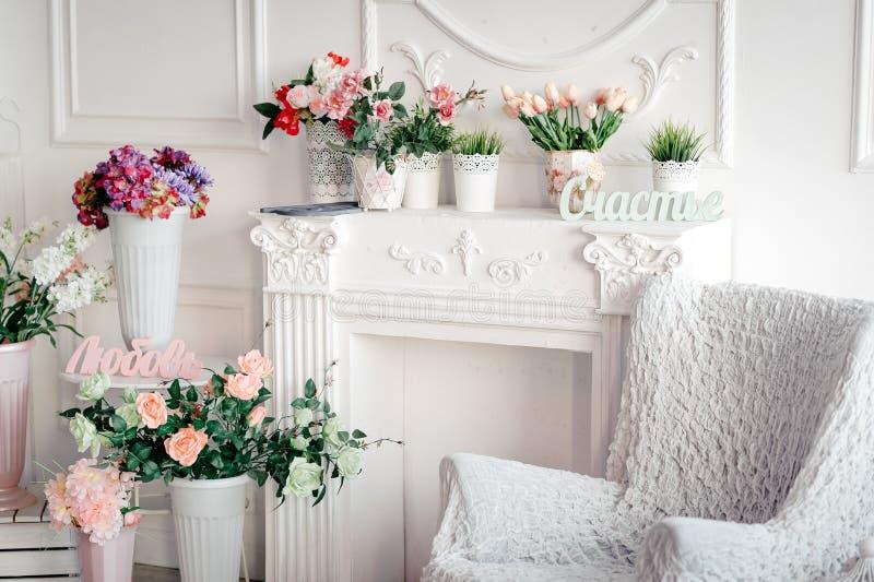 Heller Innenraum mit einem Lehnsessel und Blumen und Aufschriften im russischen Glück, Liebe stockfoto