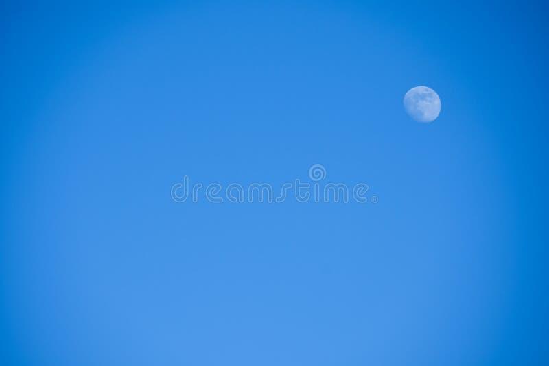 Heller kleiner voller blauer Mond gegen einen blauen Himmel am Nachmittag, Hintergrund, copyspace lizenzfreies stockbild