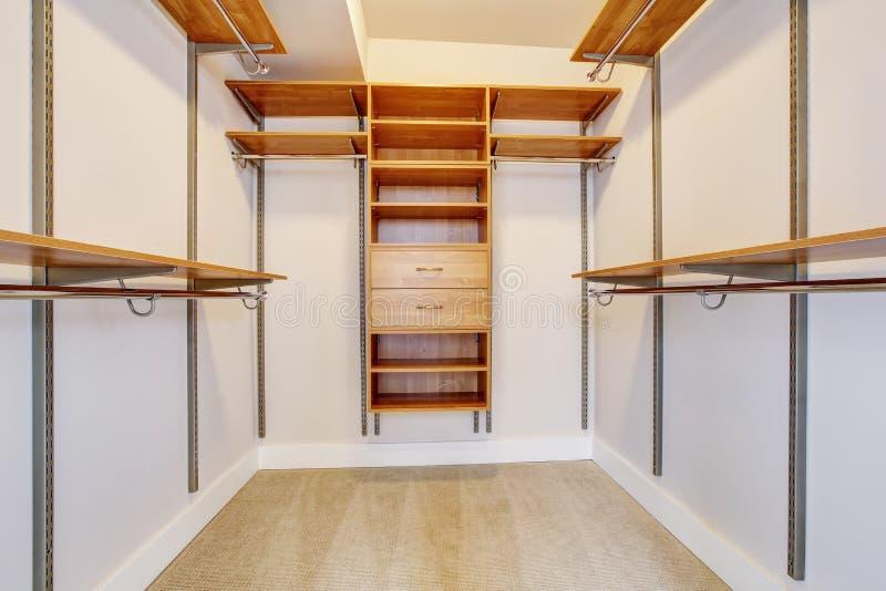 Heller leerer begehbarer Schrank mit hölzernen Regalen, beige Teppichboden stockbild