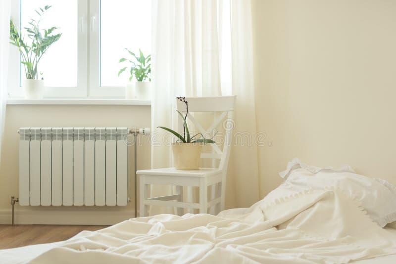 Heller Pastellschlafzimmerinnenraum, Bett, weißer Stuhl, Fenster, Lichtvorhänge lizenzfreie stockfotografie