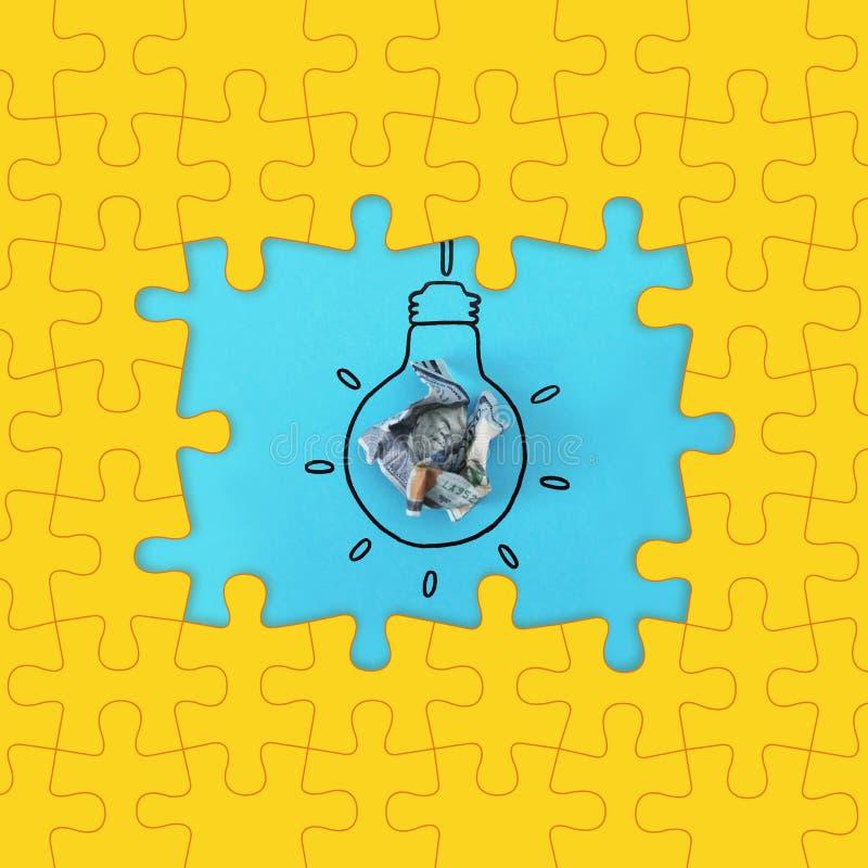 Heller Rahmen gemacht von den Puzzlespielen und von der Zusammensetzung mit zerknittertem Geld als Lampenbirne auf Farbhintergrun stockbild