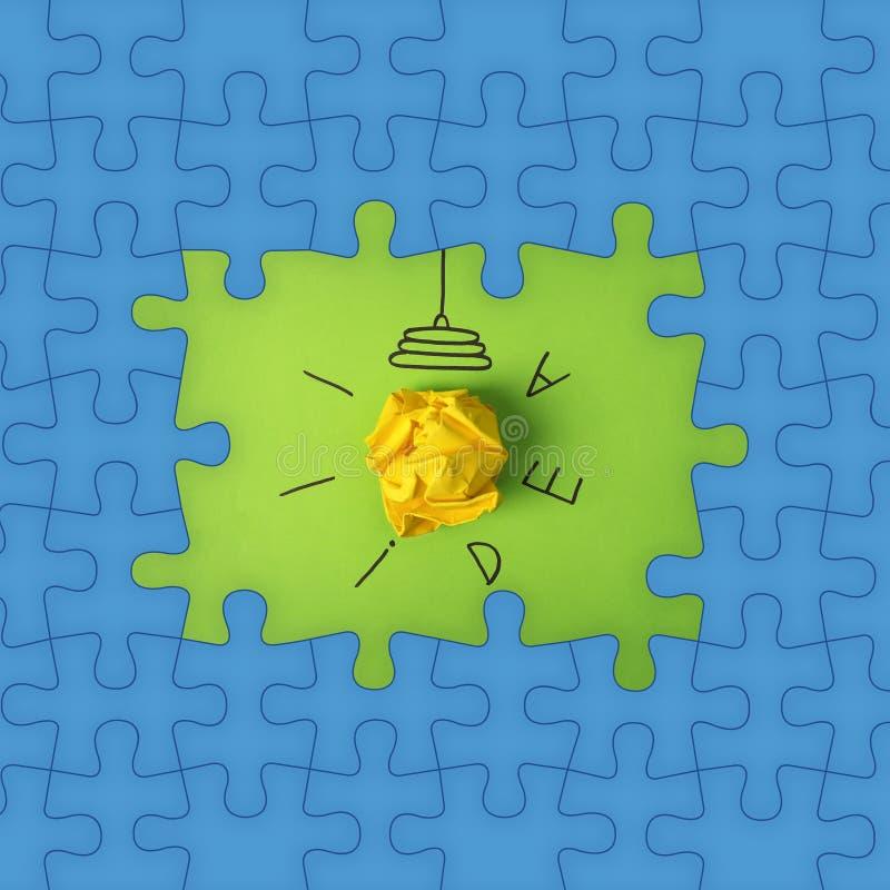 Heller Rahmen gemacht von den Puzzlespielen und von der Zusammensetzung mit zerknittertem Papierball als Lampenbirne auf Farbhint stockbilder