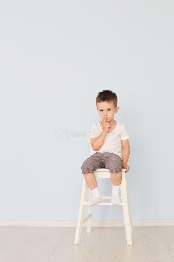 Heller Raum Junge im weißen Hemd, das in einem Hochstuhl sitzt lizenzfreie stockbilder