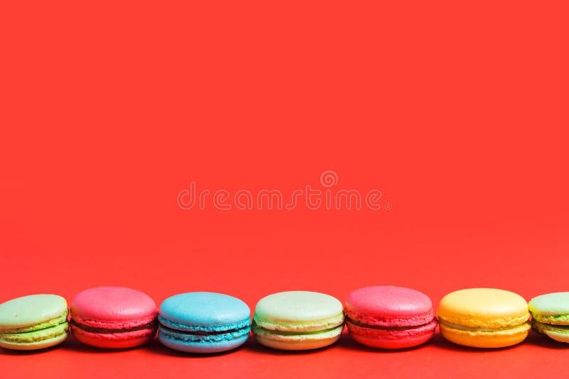 Heller roter Hintergrund für Text mit bunten gelben, grünen, blauen, rosa Makronen Kopienraum für Patissier, Café lizenzfreie stockfotografie