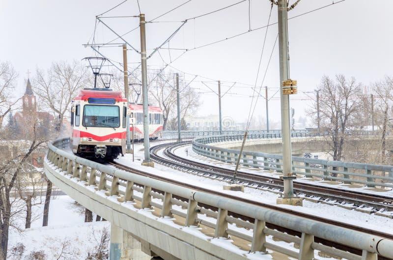 Heller Schienen-Zug auf einer kurvenden Brücke an einem Tag des verschneiten Winters stockbilder