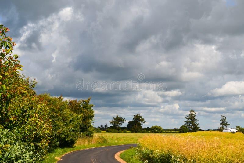 Heller Sonnenschein und große Regenwolken über der Straße in Dänemark lizenzfreie stockfotografie