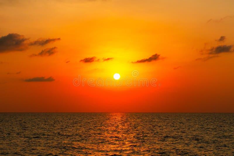 Heller Sonnenuntergang mit großer gelber Sonne unter der Oberfläche für Hintergründe stockbild