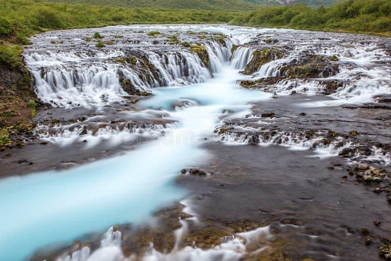 Heller starker Bruarfoss-Wasserfall in Island mit cyan-blauem Wasser stockbilder
