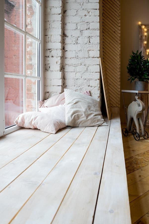 Heller Studioinnenraum mit großem Fenster, hohe Decke, Bretterboden Dachboden-Art-Schlafzimmer-Innenarchitektur Beige Kissen und lizenzfreies stockfoto