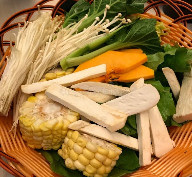 Heller und saftiger Mais, Kopfsalat, Pilze schnitt in Scheiben und in Streifen in einer Weidenplatte stockfoto