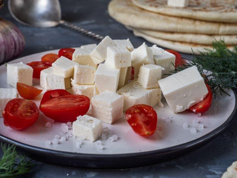 Heller und schneller Imbiss mit Tomaten- und Fetascheiben, Dillzweige, Knoblauchknolle, Teelöffel, Nahaufnahme auf grauem Hinterg lizenzfreies stockfoto