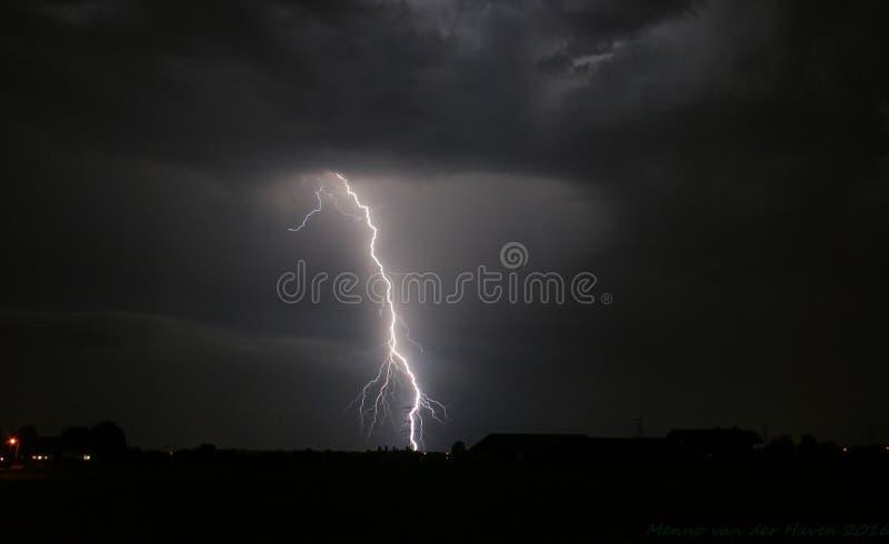 Heller verzweigter Blitzschlag nahe einem Strommast von einem schweren Gewitter in den Niederlanden lizenzfreies stockfoto