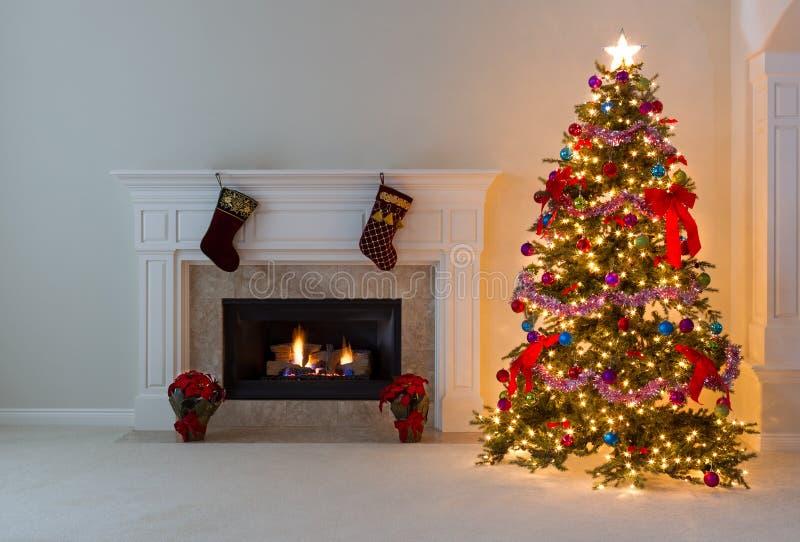 Heller Weihnachtsbaum mit brennendem Kamin lizenzfreie stockfotografie