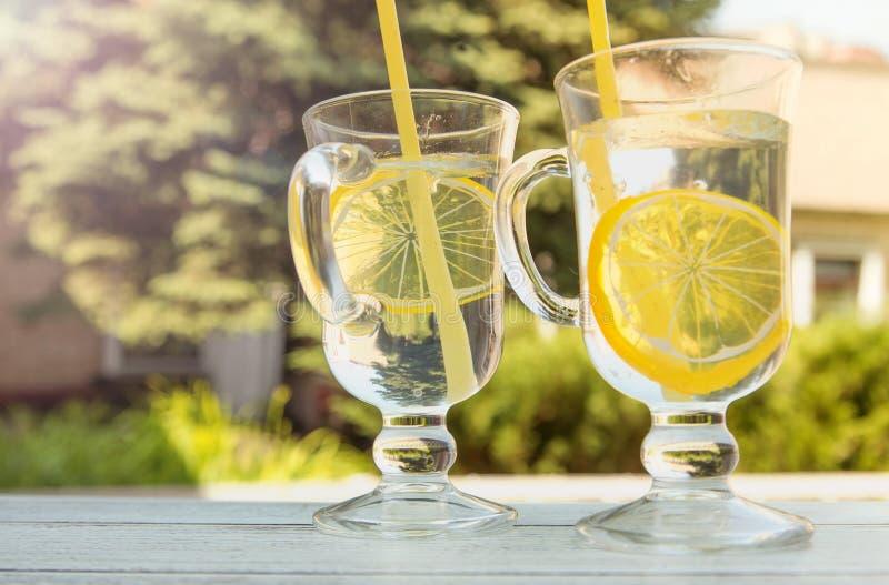Helles Auffrischungsgetränk mit Zitrone auf dem grünen Hintergrund stockbild