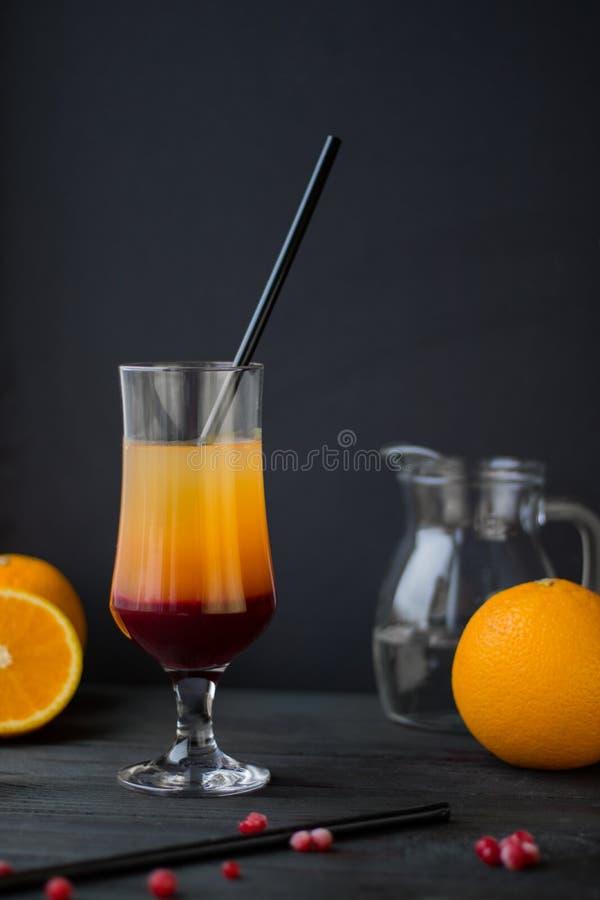 Helles ayer Orange und Beere rotes coctail mit Stroh auf dem schwarzen Hintergrund stockfotos