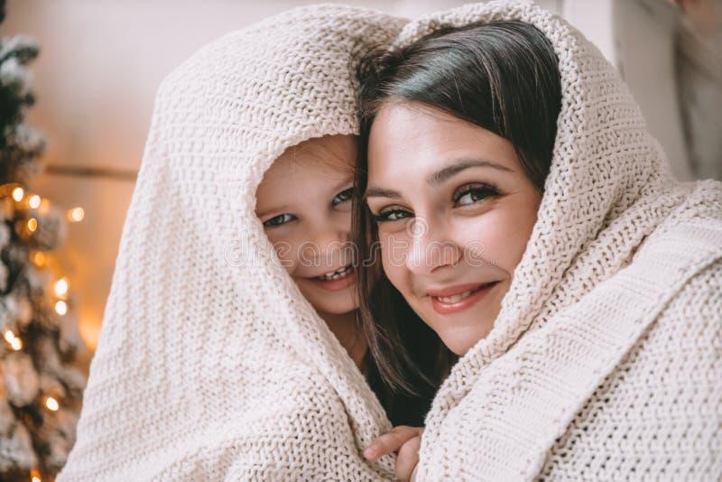 Helles Bild des Umarmens der Mutter und der Tochter in Form eines Herzens stockfotografie