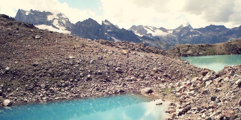 Helles blaues Wasser im alpinen See - Retro- Filterfoto stockbilder