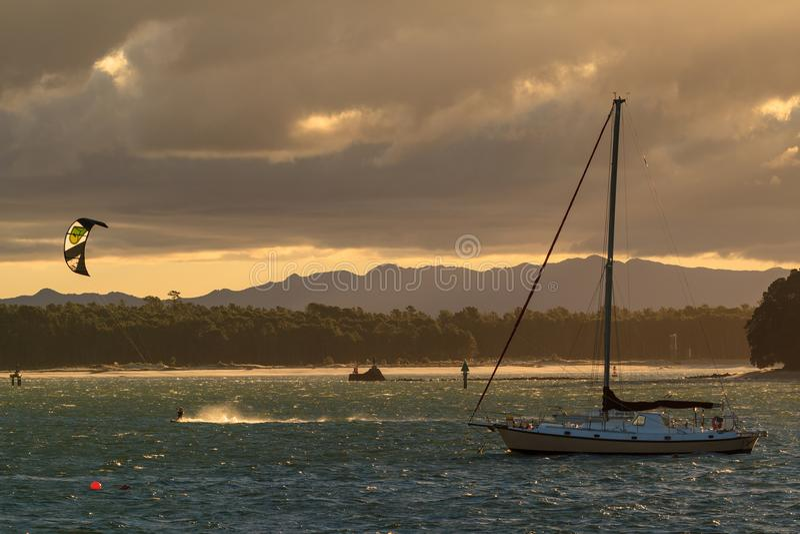 Helles Brechen des Sonnenuntergangs durch stürmische Wolken über Bucht stockbilder