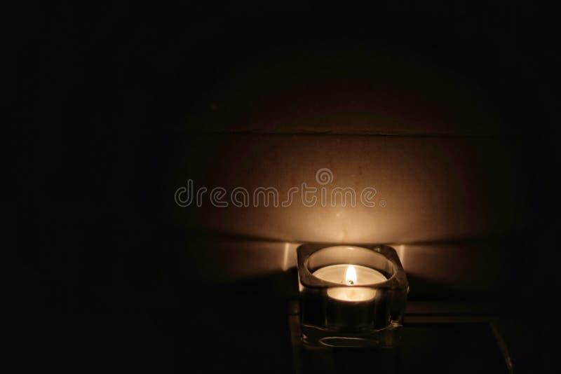 Helles Erhellen der Kerze in der Dunkelheit stockbilder