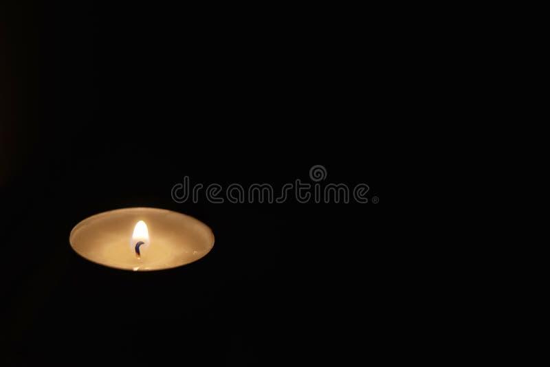 Helles Erhellen der Kerze in der Dunkelheit lizenzfreie stockbilder