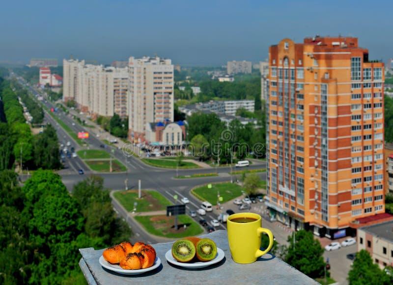 Helles Frühstück mit einem Panoramablick der Stadt: ein rötliches Brötchen mit Mohn, ein paar frischen Kiwis und einem Becher Kaf stockbilder