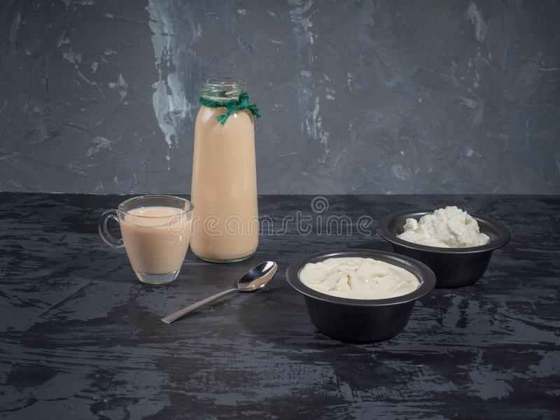Helles Frühstück von Milchprodukten des Hüttenkäses, Sahne, Milch in den schwarzen Vasen lizenzfreie stockfotos