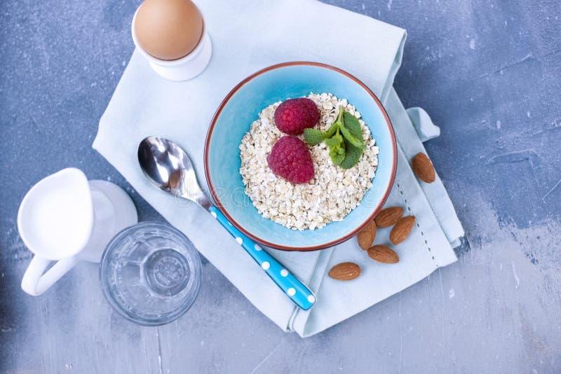 Helles Frühstück zu Hause, eine Schüssel Hüttenkäse mit Beeren von roten Himbeeren und Korinthen Blaue Serviette und Löffel Freie stockfoto