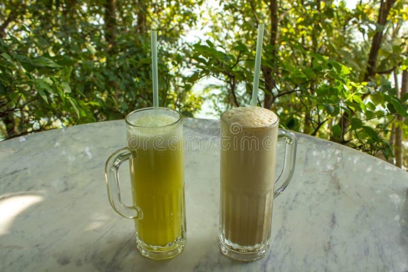Helles Gelb und Milchshaken in zwei Gläsern mit Griffen und Röhrchen auf einer weißen Marmortabelle auf einem unscharfen Hintergr lizenzfreies stockbild