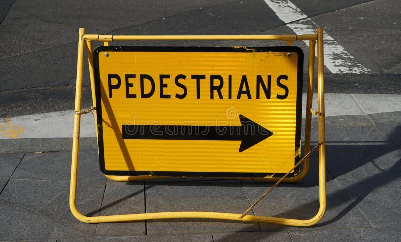 Helles gelbes Verkehrsschild mit dem Pfeil, der Fußgängerüberbrückungsrichtung anzeigt stockbilder