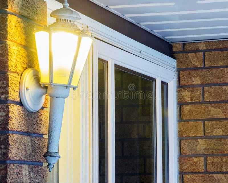 Helles Glühen des eleganten aufwändigen Portals durch die Haustür, begrüßend stockfoto