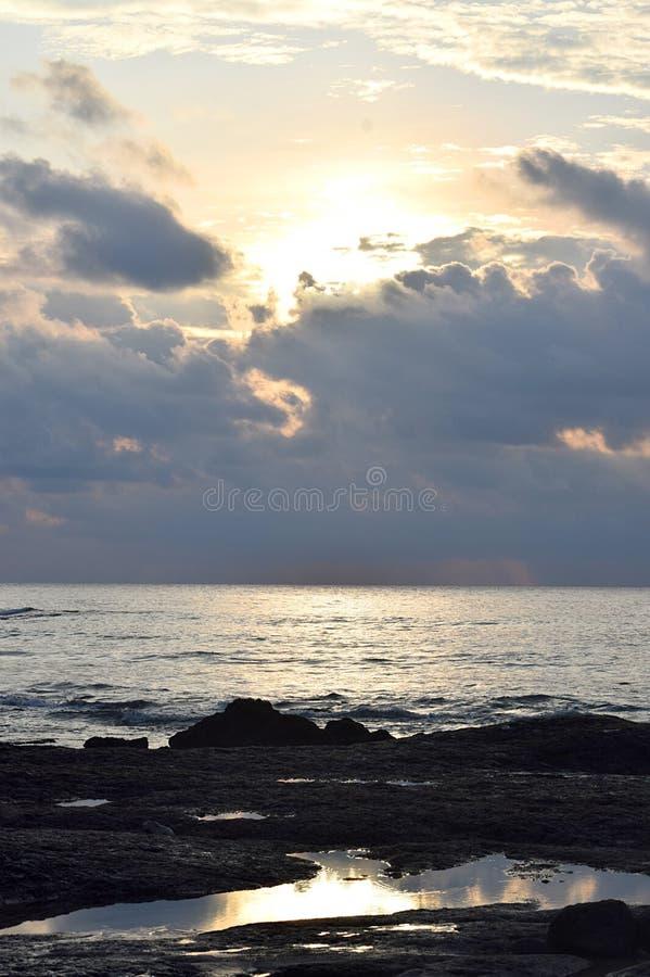 Helles goldenes Sonnenlicht, das von hinten dunkle Wolken über weitem Ozean mit Reflexion in der Pfütze - Laxmanpur, Neil Island, lizenzfreie stockfotos
