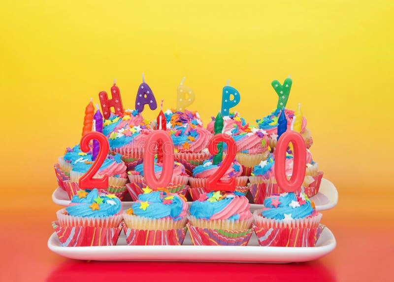 Helles guten Rutsch ins Neue Jahr 2020 der kleinen Kuchen mit Kerzen lizenzfreie stockbilder