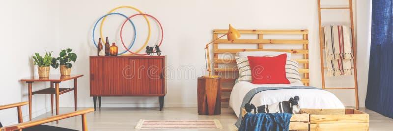 Helles Jugendlichschlafzimmer im wirklichen Foto mit Retro- Schrank stockfotografie