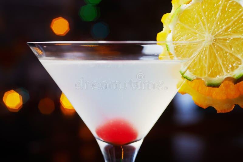 Helles köstliches Cocktail mit Dekoration von Stücken der Orange und der Kirsche an der Unterseite des Glases auf dem Tisch im re lizenzfreie stockfotografie