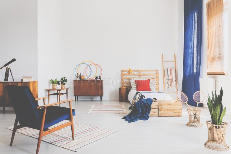 Helles Oldschool-Jugendlichschlafzimmer mit Weinlesemöbeln, wirkliches Foto mit Kopienraum auf der Wand lizenzfreies stockbild