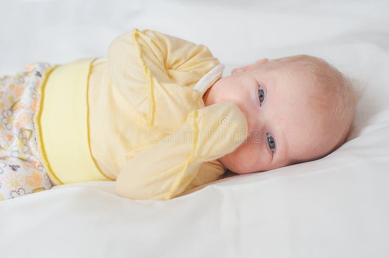Helles Porträt des netten Babys mit den Fingern im Mund im weißen Bett stockbilder