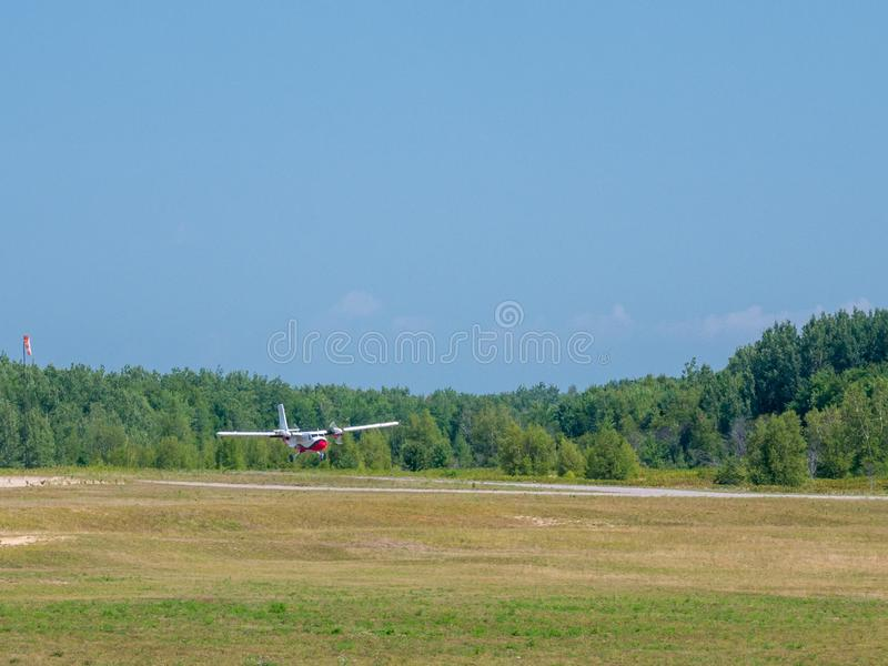 Helles Privatflugzeug landet auf einem kleinen Flugplatz an einem sonnigen Sommertag lizenzfreies stockfoto