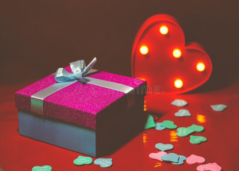 Helles rosa Geschenk mit einem Bogen auf einem roten Hintergrund mit Dekorationen von den mehrfarbigen Herzen lizenzfreie stockbilder