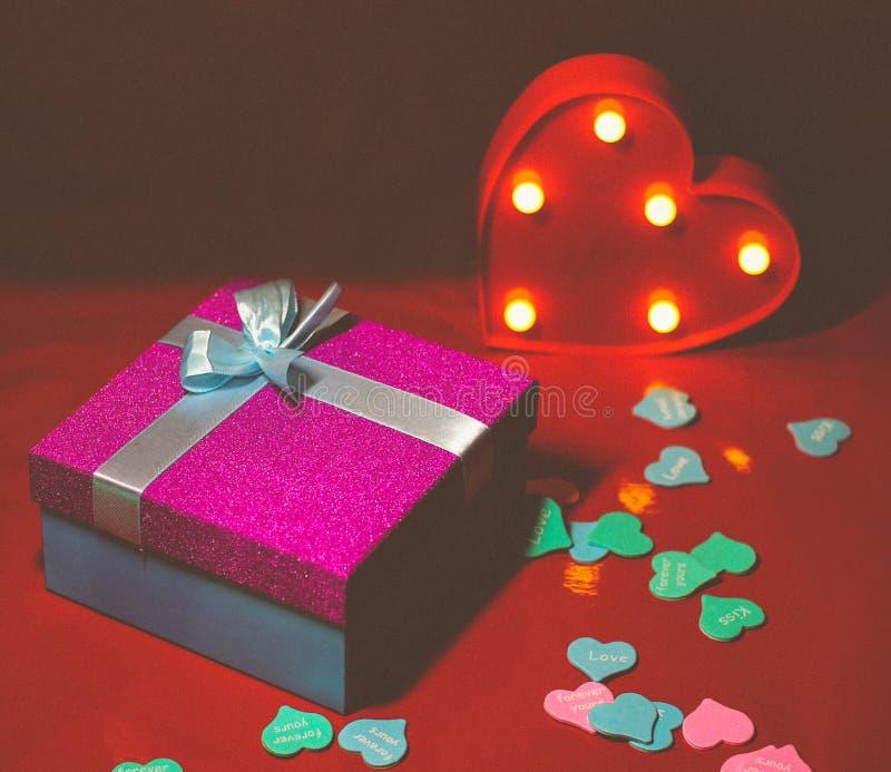 Helles rosa Geschenk mit einem Bogen auf einem roten Hintergrund mit Dekorationen von den mehrfarbigen Herzen stockbilder