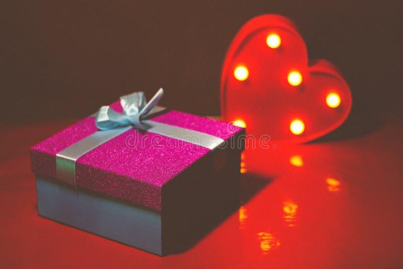 Helles rosa Geschenk mit einem Bogen auf einem roten Hintergrund mit Dekorationen von den mehrfarbigen Herzen lizenzfreie stockfotos