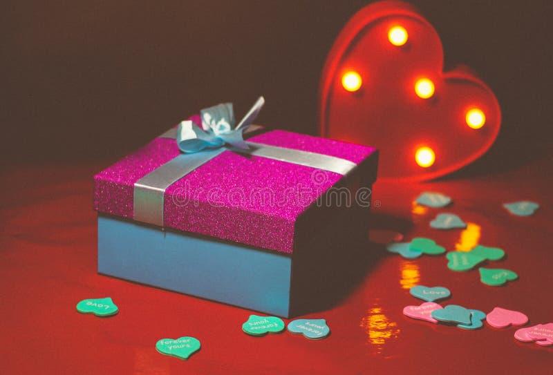 Helles rosa Geschenk mit einem Bogen auf einem roten Hintergrund mit Dekorationen von den mehrfarbigen Herzen stockfotografie