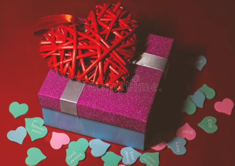 Helles rosa Geschenk mit einem Bogen auf einem roten Hintergrund mit Dekorationen von den mehrfarbigen Herzen lizenzfreies stockbild
