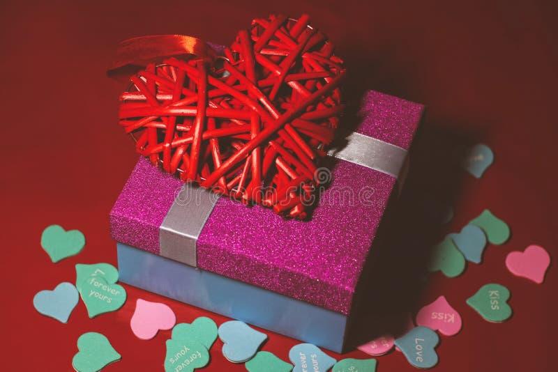 Helles rosa Geschenk mit einem Bogen auf einem roten Hintergrund mit Dekorationen von den mehrfarbigen Herzen stockfotos