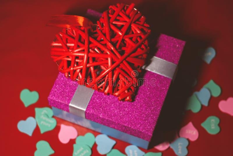 Helles rosa Geschenk mit einem Bogen auf einem roten Hintergrund mit Dekorationen von den mehrfarbigen Herzen lizenzfreie stockfotografie