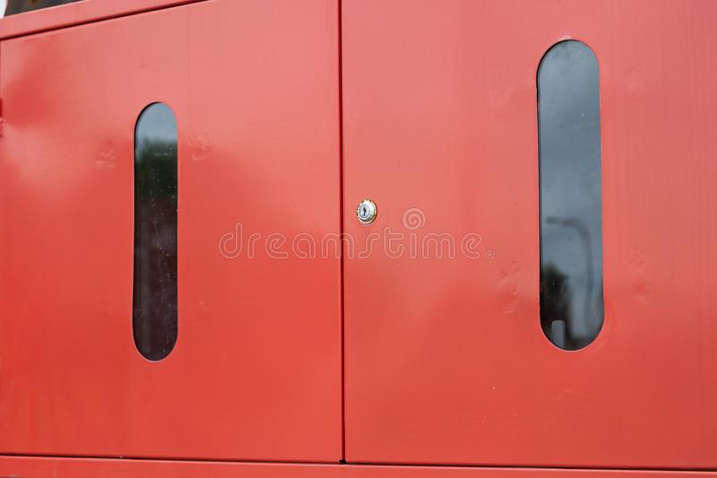 Helles rotes orange Metall schloss Feuerlöscher-Schranktüren draußen am Gebäudeeingang zu lizenzfreie stockfotografie