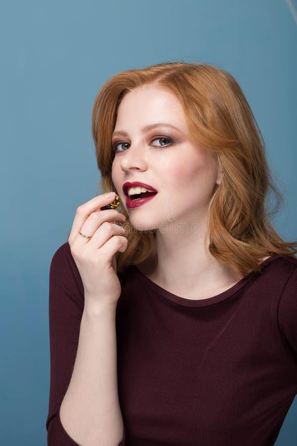 Helles schönes sexy Rothaarigemädchen isst mit bunter Süßigkeitsnahaufnahme der geschlossenen Augen, blauer Hintergrund, Make-up lizenzfreies stockbild