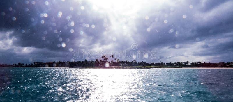 Helles Sonnenlicht, welches aus die Sturmwolken herauskommt und über Tröpfchen nachdenkt stockfotografie