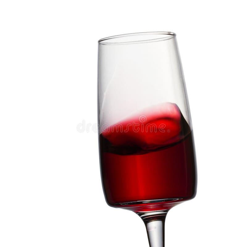 Helles Spritzen des Rotweins und des schönen Glases stockfoto