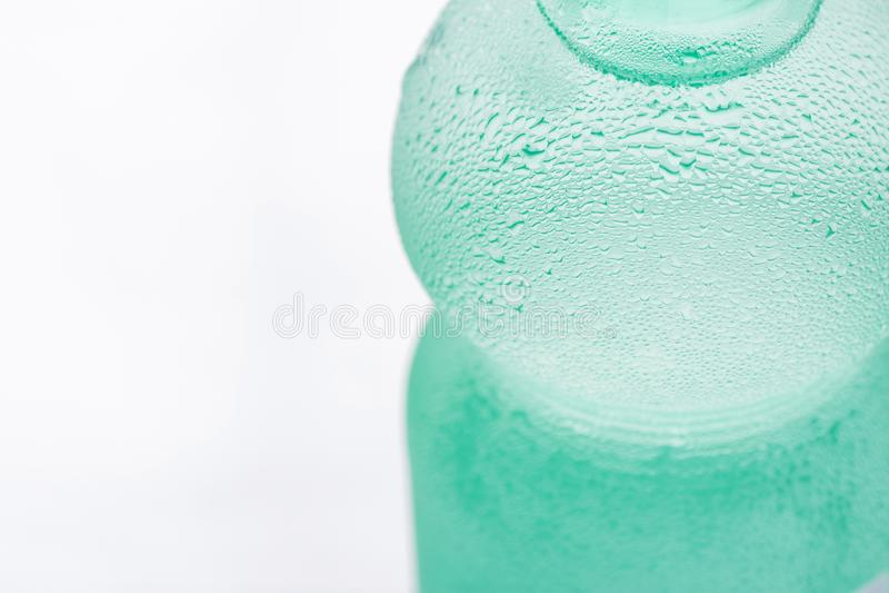 Hellgrünes geschwitztes Frosty Bottle mit klarem reinem kaltem Wasser auf weißem Hintergrund Hydratations-Sommer-Erfrischung stockfoto